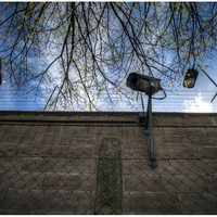 Outside the prison wall, a fence in front and surveillance camera.